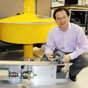 Lei Zuo, associate professor of mechanical engineering, holds the first iteration of a mechanism designed to harvest wave energy. The larger version at his feet will use a multi-directional system that gathers energy as waves move back and forth. The apparatus will be housed in a buoy similar to the yellow one behind him.