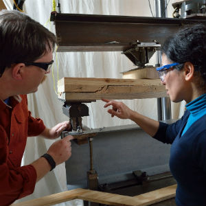 Daniel Hindman, left, and doctoral student Houri Sharifniay examine failures in a southern pine cross-laminated timber beam during testing at the Brooks Forest Products Laboratory.