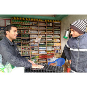 Sammar Regmi, left, owner of Laxmi Agrovet in Mehelkuna, Nepal, discusses seed trays with a customer. Thanks to the training he's received from the Integrated Pest Management Innovation Lab, he can offer information on the products he sells.