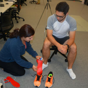 Mackenzie Wenrick places sensors in a research participant's shoes to measure force while he runs.