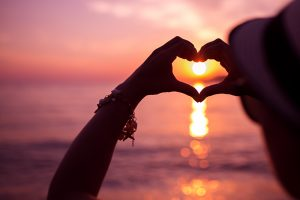 Woman making heart of hands near sea at sunset
